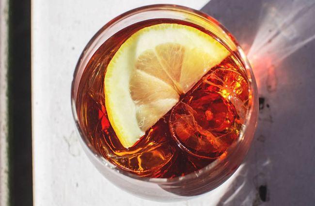 vaso de vermut rojo con rodaja de limón